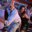 Stock Photo: Senior MDancing With Younger WomIn Busy Bar