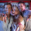 Senior Woman Having Fun In Busy Bar With Two Young Men — Stock Photo #11880937