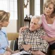 Stock Photo: Senior Couple Talking To Health Visitor At Home
