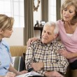 Senior Couple Talking To Health Visitor At Home — Stock Photo