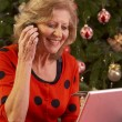Senior Woman Shopping Online For Christmas Gifts On Phone - Stock Photo