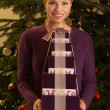 Woman Holding Christmas Gifts In Front Of Tree — Foto Stock #11881090