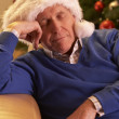 Tired Senior Man Relaxing In Front Of Christmas Tree — Stock Photo