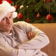 Man Relaxing In Front Of Christmas Tree - Stock Photo