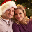 Royalty-Free Stock Photo: Couple Relaxing In Front Of Christmas Tree