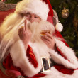 Santa Claus Making Rude Gesture To Camera In Front Of Christmas Tree - Stock Photo