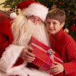 Santa Claus Giving Gift To Boy In Front Of Christmas Tree — Stock Photo #11881123