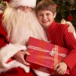 Santa Claus Giving Gift To Boy In Front Of Christmas Tree — Stock Photo