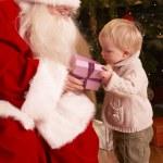 Papá Noel regalo a niño delante de árbol de Navidad — Foto de Stock