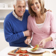 Senior Couple Making Sandwich In Kitchen - 图库照片