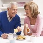 starší pár, kteří požívají horký nápoj v kuchyni — Stock fotografie #11881154