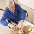 Disabled Senior Man Making Sandwich In Kitchen — Stok fotoğraf
