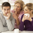 Senior Mother Interferring With Couple Having Argument At Home - Foto Stock