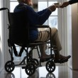 Stock Photo: Disabled Senior MSitting In Wheelchair Being Handed Cup