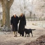 couple de personnes âgées sur hiver marche avec le chien à travers le paysage givré — Photo