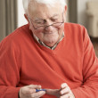 Senior Man Checking Blood Sugar Level At Home — Stock Photo
