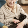 Stock Photo: Senior WomRelaxing In Chair At Home With Pet Cat