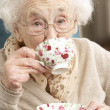 Senior Woman Enjoying Cup Of Tea At Home — Stock fotografie #11881295