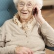 Senior Woman Talking On Mobile Phone Sitting In Chair At Home — Stock Photo #11881309