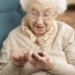 Senior Woman Dialling Number On Mobile Phone Sitting In Chair At — 图库照片