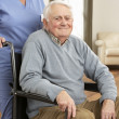 Disabled Senior Man Sitting In Wheelchair With Carer Behind — Stock Photo