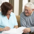 Senior Man In Discussion With Health Visitor At Home — Stock Photo