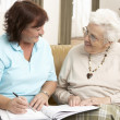 Senior Woman In Discussion With Health Visitor At Home — Stock Photo