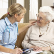 donna senior in discussione con il visitatore di salute a casa — Foto Stock
