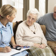 Senior Couple In Discussion With Health Visitor At Home — Stock Photo #11881335