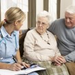 Senior Couple In Discussion With Health Visitor At Home — Stok fotoğraf