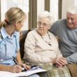 Stock Photo: Senior Couple In Discussion With Health Visitor At Home