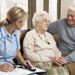 Royalty-Free Stock Photo: Senior Couple In Discussion With Health Visitor At Home