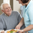 Senior Man Being Served Meal By Carer — Foto Stock