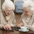 Two Senior Women Playing Dominoes At Day Care Centre - Stock Photo