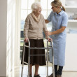 Carer Helping Elderly Senior Woman Using Walking Frame - Stockfoto