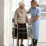 verzorger helpen ouderen senior vrouw met behulp van wandelen frame — Stockfoto
