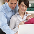 Parents With Newborn Baby Working From Home Using Laptop — Stock Photo #11881425