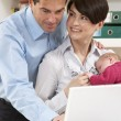 Parents With Newborn Baby Working From Home Using Laptop - Photo