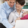 Parents With Newborn Baby Working From Home Using Laptop - Stock Photo