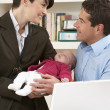 Working Mother Leaving Baby With Father Who Works From Home - Stock Photo