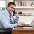 Man Working From Home Using Laptop On Phone — Stock Photo