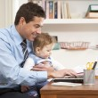 Stock Photo: MWith Baby Working From Home Using Laptop