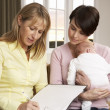 Mother With Newborn Baby Talking With Health Visitor At Home — Foto de Stock