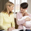 Mother With Newborn Baby Talking With Health Visitor At Home — Stock Photo
