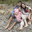 Family on beach with blankets - ストック写真