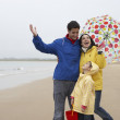 Happy family on beach with umbrella — Stock Photo #11881615