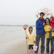 Stock Photo: Happy family on beach with umbrella