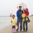 图库照片: Happy family on beach with umbrella