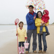 Happy family on beach with umbrella — Stock Photo #11881622