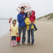 Happy family on beach with umbrella — Stock Photo #11881623